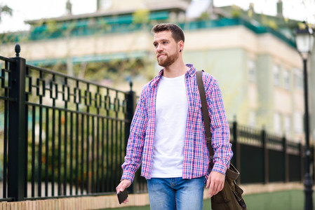 Young bearded man walking in urban background Lifestyle concept