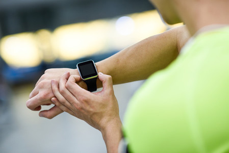 Young man using smartwatch at the gym