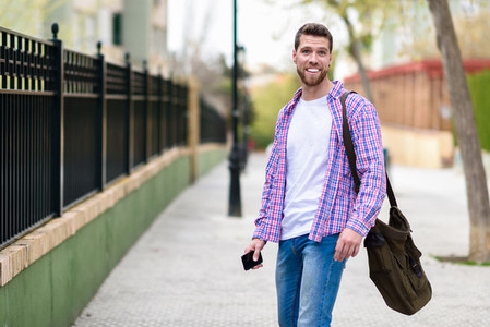 Young bearded man smiling in urban background  Lifestyle concept