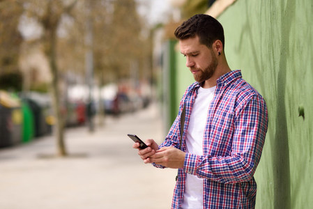 Young man looking his smart phone in urban background  Lifestyle