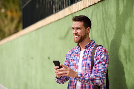 Young man laughing with his smart phone in urban background  Lif