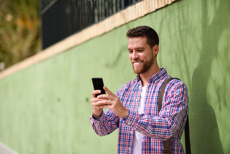 Young man looking at his smart phone in urban background Lifest