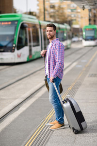 Young man waiting his train in urban subway station  Lifestyle c