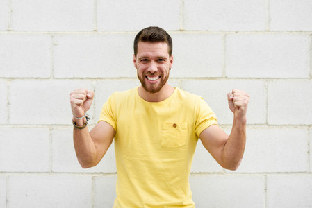 Funny young man on brick wall with funny expression