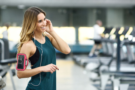Young woman using smartphone standing in the gym