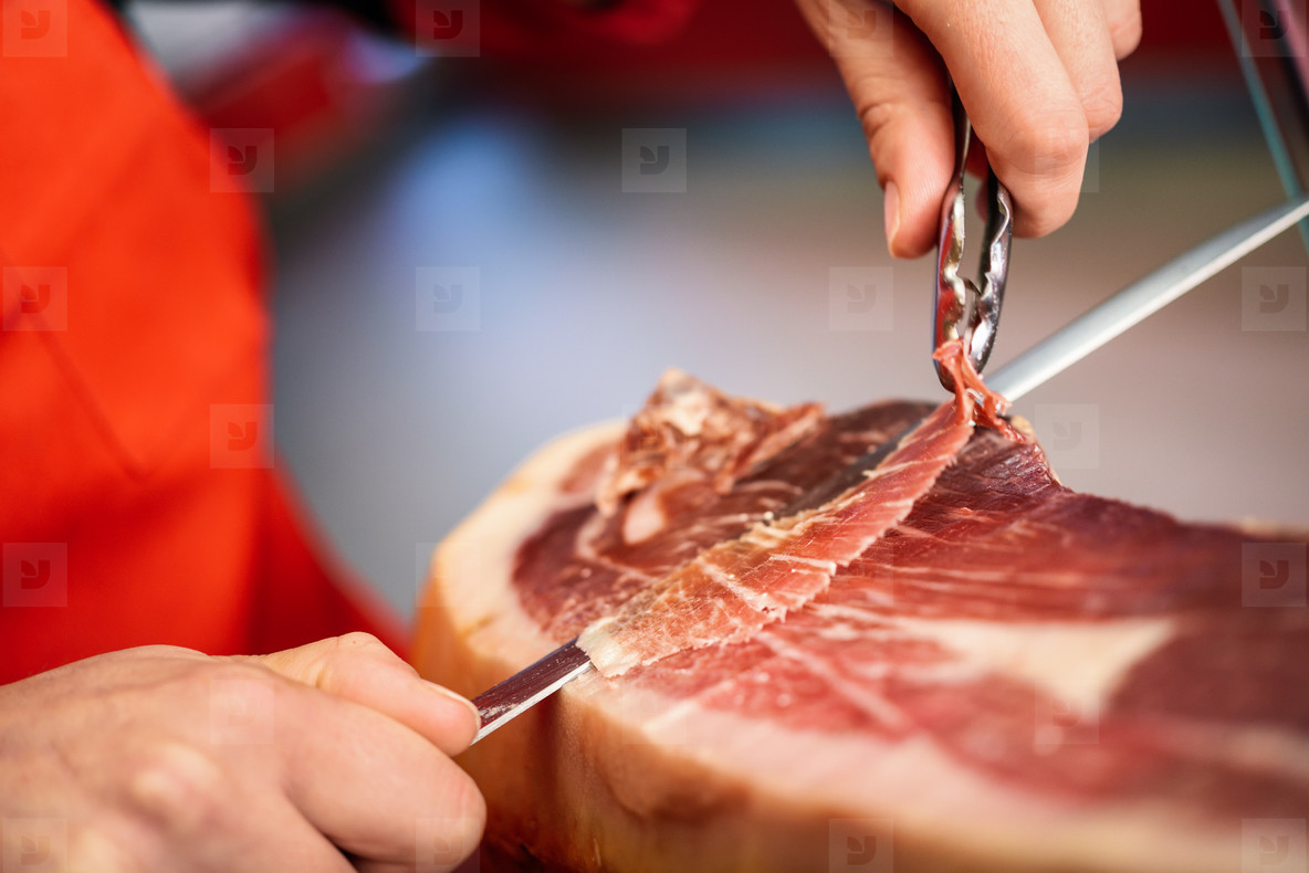 Professional cutter carving slices from a whole bone in serrano