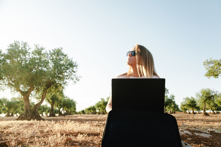 Young woman with a laptop case seated in the olive tree field