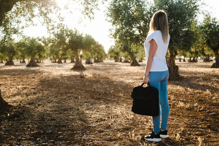 Young woman with a laptop case through the olive tree field