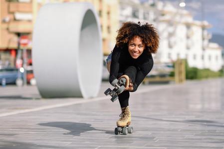 Black woman on roller skates riding outdoors on urban street