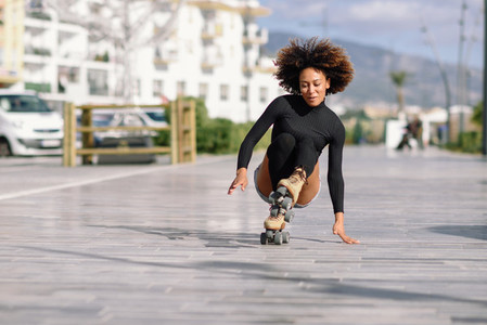Black woman on roller skates falling to the ground