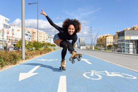 Black woman on roller skates riding on bike line