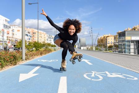 Black woman on roller skates riding on bike line