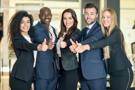 Group of businesspeople with thumbs up gesture in modern office