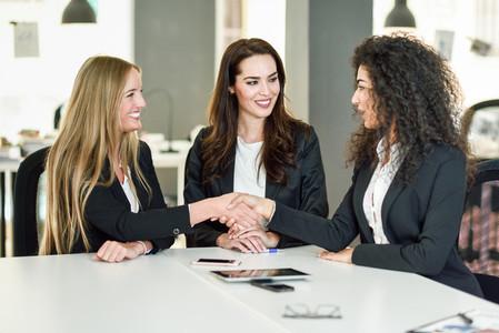 Three businesswomen shaking hands in a modern office