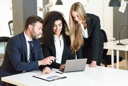 Multi ethnic group of three businesspeople meeting in a modern o