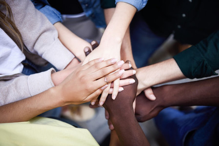 Top view of young people putting their hands together