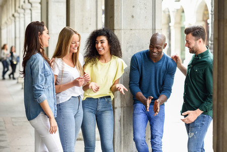 Multi ethnic group of friends having fun together in urban backg