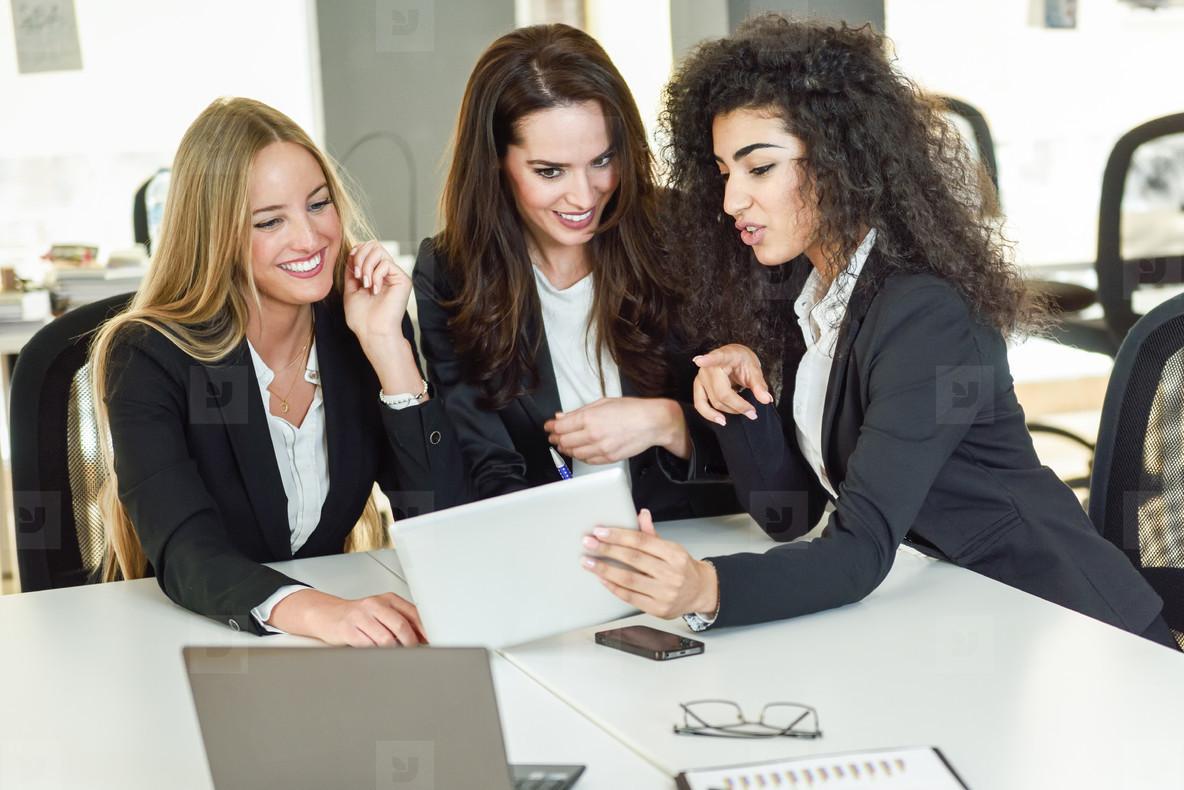 Three businesswomen working together in a modern office