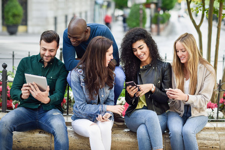 Multi ethnic young people using smartphone and tablet computers outdoors