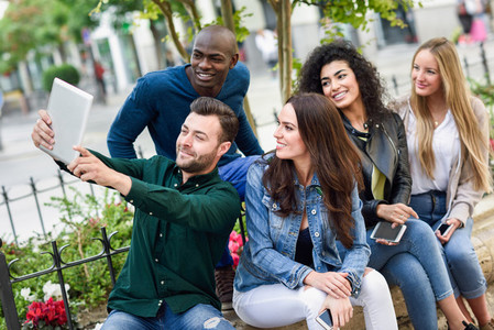 Multi ethnic young people taking selfie together in urban background