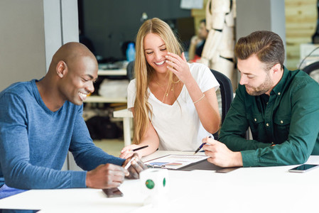 Multi ethnic group of three young people studying and smiling to