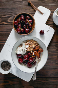 Healthy summer vegetarian breakfast with granola cherry pecans coconut flakes chia and oat milk Flat lay top view