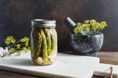 Pickled asparagus in a glass jar on a white marble tray Seasonal canning vegetable recipe