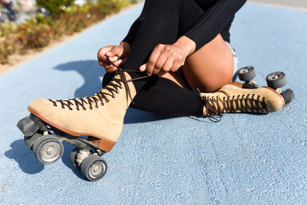 Unrecognizable black girl sitting on bike line and puts on skate