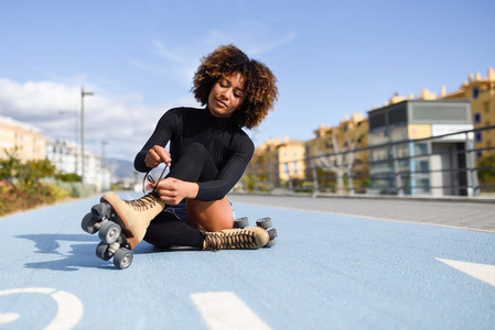 Young smiling black girl sitting on bike line and puts on skates