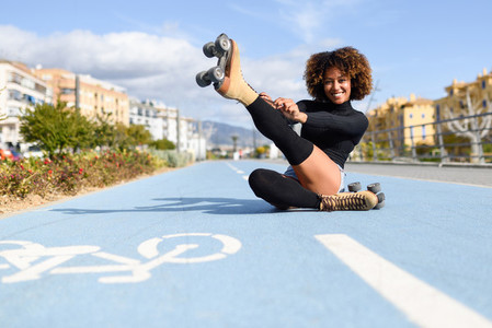 Funny smiling black girl sitting on bike line and puts on skates