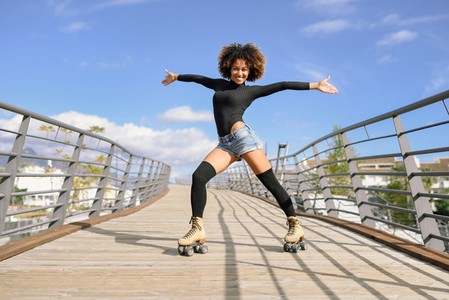 Afro hairstyle woman on roller skates riding outdoors on urban b