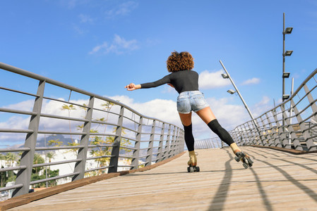 Rear view of black woman on roller skates riding on urban bridge