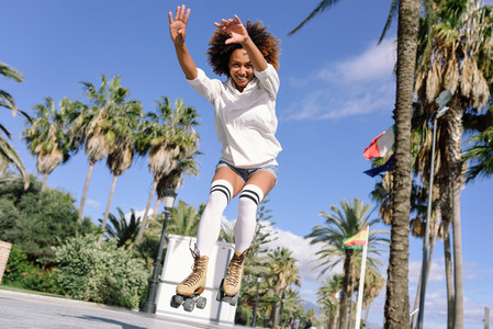 Black woman  afro hairstyle  on roller skates jumping near the b