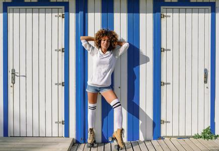 Young black woman on roller skates near a beach hut