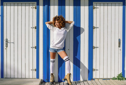 Young black woman on roller skates near a beach hut