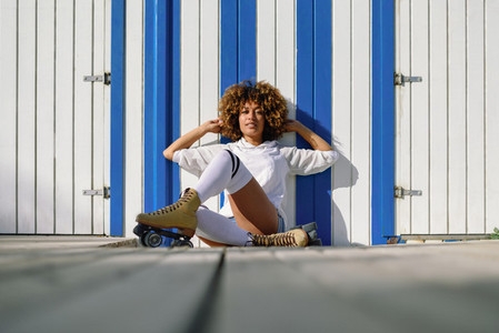 Young black woman on roller skates sitting near a beach hut