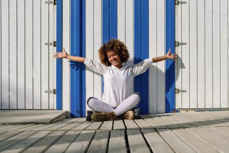 Young black woman on roller skates sitting near a beach hut