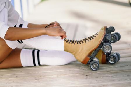 Close up of black girl sitting on wooden floor puts on skates