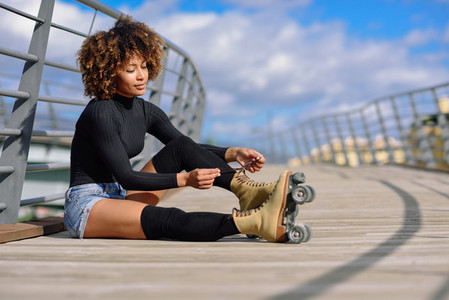 Young smiling black girl sitting on urban bridge and puts on ska