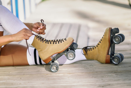 Close up of black girl sitting on wooden floor puts on skates