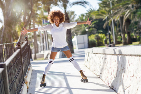Black woman  afro hairstyle  on roller skates riding near the be