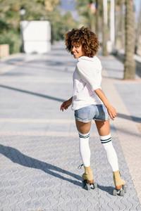 Black woman on roller skates rollerblading in beach promenade wi