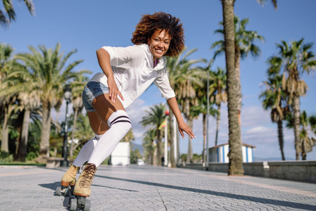 Black woman on roller skates rollerblading in beach promenade wi