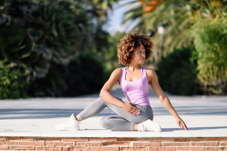 Black woman afro hairstyle doing yoga on promenade