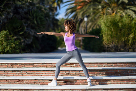 Black woman  afro hairstyle  doing yoga in warrior pose