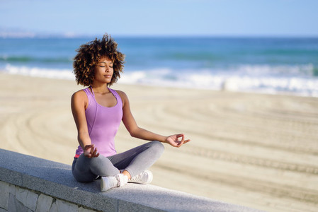 Black woman  afro hairstyle  in lotus pose with eyes closed in the beach