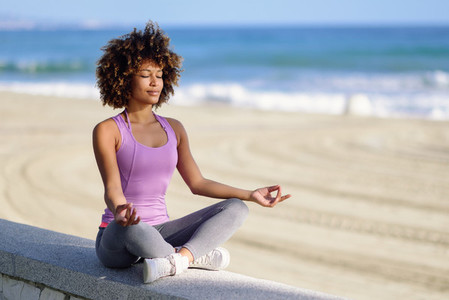 Black woman afro hairstyle in lotus asana with eyes closed in the beach