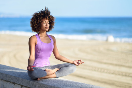 Black woman  afro hairstyle  in lotus pose with eyes closed in t