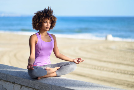 Black woman  afro hairstyle  doing yoga in the beach