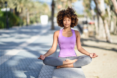 Black woman afro hairstyle in lotus asana with eyes closed in
